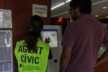 una persona que realitza treballs en benefici de la comunitat ensenya a un usuari el funcionament del caixer TESEO