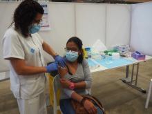 Una infermera posant la dosi addicional